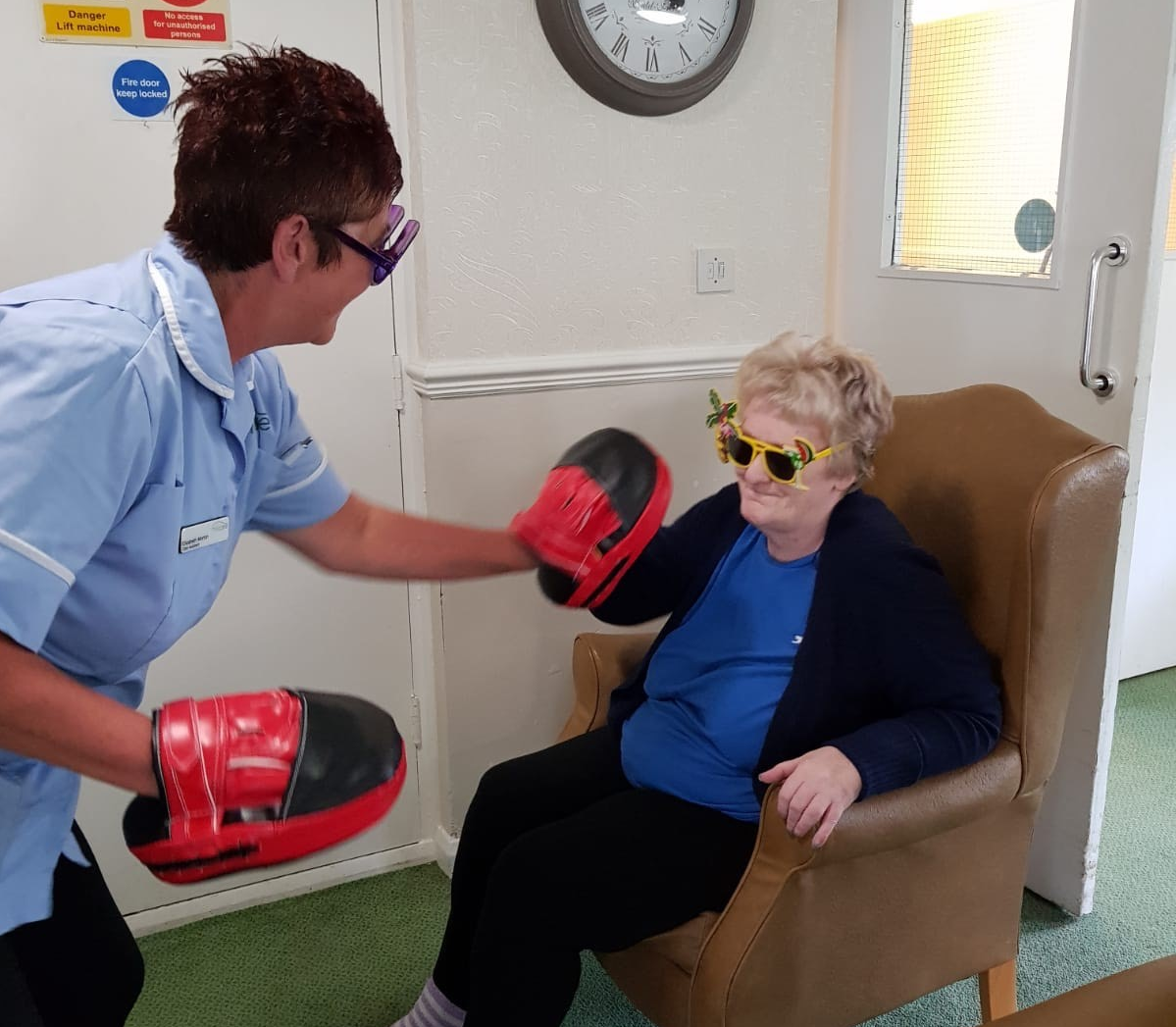 The Oaks Care Home resident Ann Lillico testing her punching power on pads held by carer Elizabeth Morton